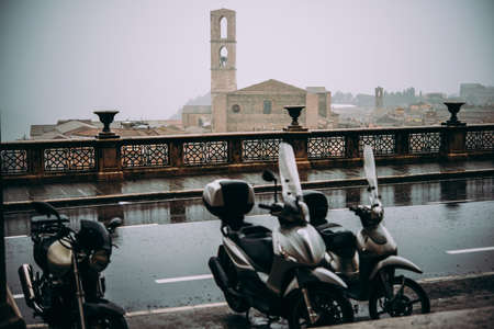 Parked motorbikes at a rainy street of Perugia, Umbria, Italy. Stock Photo
