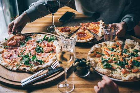 Various pizzas and glasses of wine served for dinner in a restaurant. Zdjęcie Seryjne - 102002566