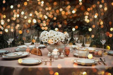 Tafel geserveerd voor een luxe etentje verlicht met slingers Stockfoto