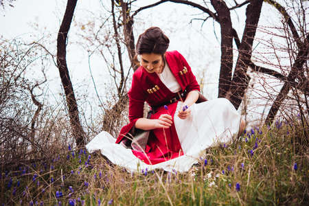 Young beautiful girl wearing traditional georgian dress picking up flowers.