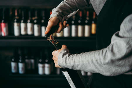 Opening a wine bottle.