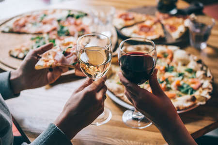 Various pizzas and glasses of wine served for dinner in a restaurant.