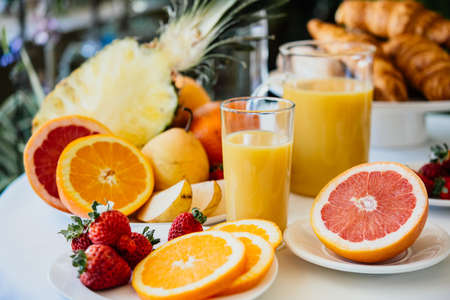 Fresh fruits and orange juice on a breakfast table Stock Photo