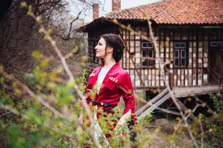 Young beautiful girl wearing traditional georgian dress stands in front of georgian house. 版權商用圖片