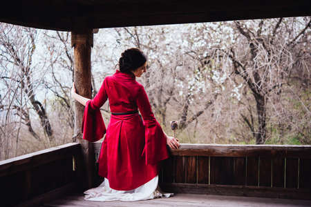 Portrait of a young beautiful girl wearing traditional georgian dress sitting on the porch. 版權商用圖片
