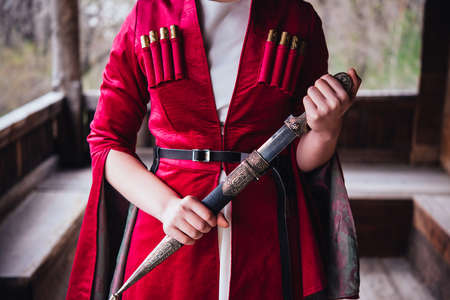 Girl wearing traditional georgian dress holding a dagger.