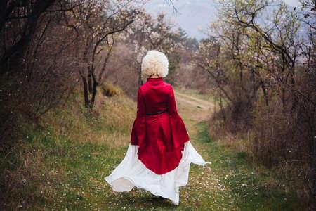Young beautiful girl wearing traditional georgian dress walks along the village. 版權商用圖片