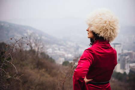 Portrait of a young beautiful girl wearing traditional georgian dress with the city in the background.