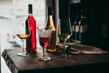 Different glasses and bottles of wine served on a wooden table in a bar or a wine shop. Reklamní fotografie - 103759200
