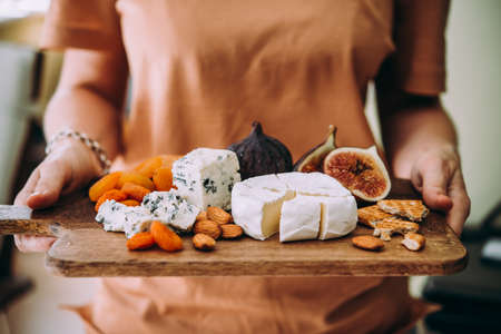 Hands holding a wooden board with different kinds of cheese and dried fruits. Dinner or aperitivo party concept.