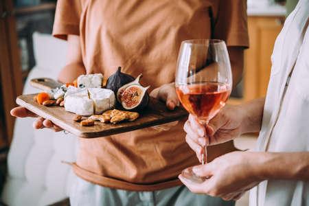 Hände halten ein Glas Wein und ein Holzbrett mit verschiedenen Käsesorten und getrockneten Früchten. Abendessen oder Aperitif Party Konzept. Standard-Bild