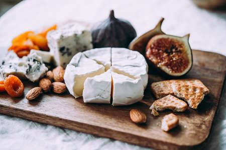 Wooden board with different kinds of cheese and dried fruits. Dinner or aperitivo party concept.