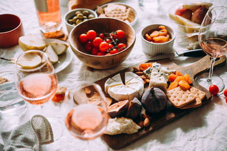 A dinner table served with different kinds of cheese,fruits and rose wine. Stock Photo