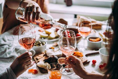Wijn gieten tijdens een etentje met vrienden.