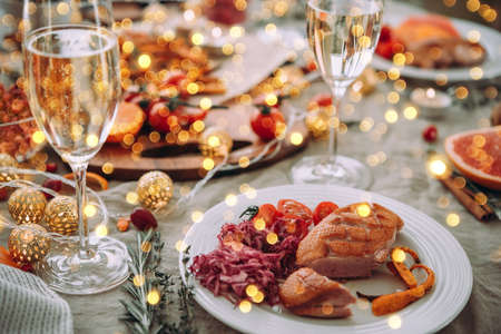 Roasted duck or turkey. Party table with glasses of champagne. Friends celebrating Christmas or New Year eve.