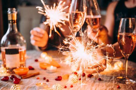 Przyjaciele świętują przyjęcie sylwestrowe z bengalskimi światłami i różanym szampanem.