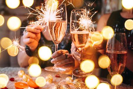 Amis célébrant la fête de Noël ou du nouvel an avec des lumières du Bengale et du champagne rose.