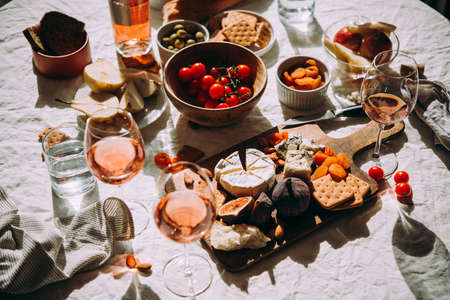 A dinner table served with different kinds of cheese,fruits and rose wine. Imagens