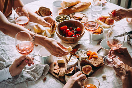 Friends having a dinner party with different kinds of appetizers and rose wine. Фото со стока - 110132262