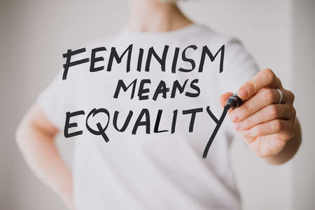 Writing hand. Woman holds pen or marker and writing Feminism means equality phrase