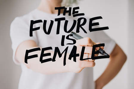 Writing hand. Woman holds pen or marker and writing The future is female phrase