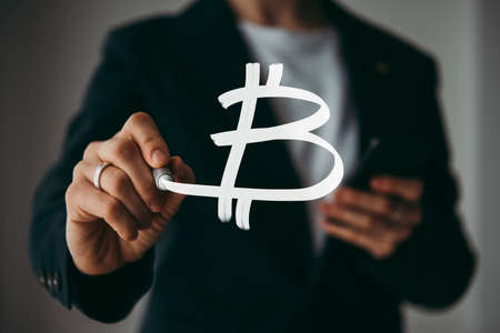 Writing hand. Business woman holds pen or marker and writing Bitcoin symbol