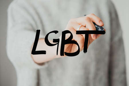 Writing hand. Woman holds pen or marker and writing LGBT abbreviature Stockfoto - 110132485