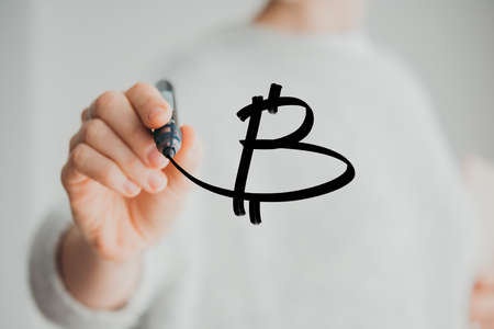 Writing hand. Woman holds pen or marker and writing Bitcoin symbol