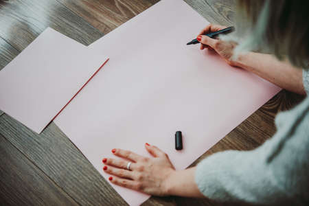 Young woman writing something on a big piece of paper
