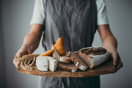 Offering cheese and bread served on a wooden board. Wine dinner or aperitivo party concept. Stock Photo