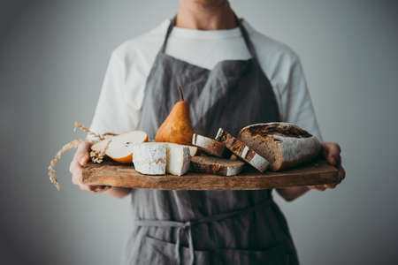 Offering cheese and bread served on a wooden board. Wine dinner or aperitivo party concept. Imagens