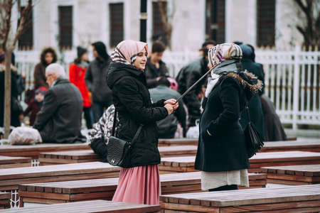 ISTANBUL, TURKEY - 29 JANUARY, 2017: Turkisg girls take pictures around the Blue Mosque in Istanbul, Turkey.