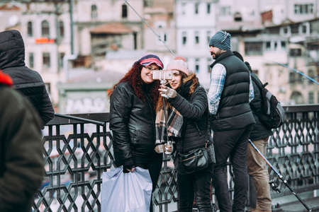 ISTANBUL, TURKEY - 29 JANUARY, 2017: Tourists take pictures at the Galata bridge in Istanbul, Turkey.