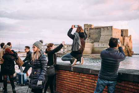 NAPLES, ITALY - 18 DECEMBER, 2017: People taking photos at the seaside in Naples, Campania, Italy. Publikacyjne