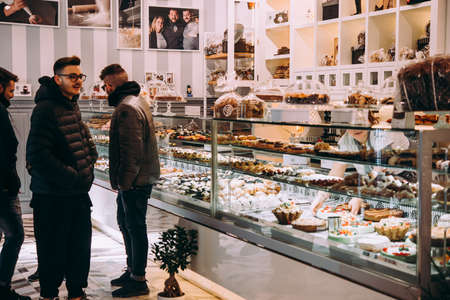 NAPLES, ITALY - 18 DECEMBER, 2017: People buy sweets in one of the bakeries of Naples, Campania, Italy. Editorial