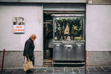 NAPLES, ITALY - 18 DECEMBER, 2017: An elderly woman passing by a butchery in Naples, Campania, Italy.