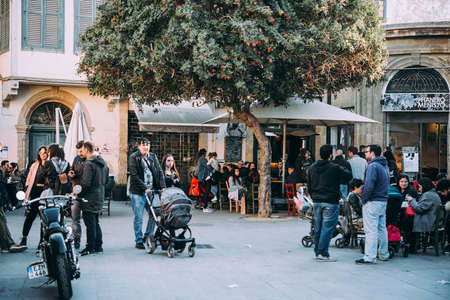 NICOSIA, CYPRUS - 18 MARCH, 2017: People sit in street cafes and walk along one of the streets of Nicosia, Cyprus.