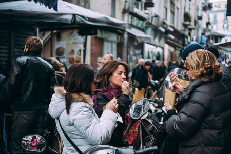 NAPLES, ITALY - 17 DECEMBER, 2017: People enjoy street food in Naples, Campania, Italy.