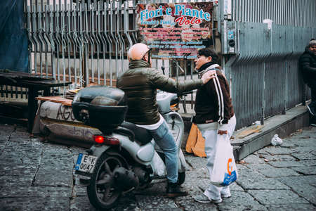 NAPLES, ITALY - 17 DECEMBER, 2017:People have a friendly chat in the streets of Naples, Campania, Italy.