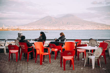 NAPLES, ITALY - 18 DECEMBER, 2017: People enjoy relaxing at the seaside in Naples, Campania, Italy.