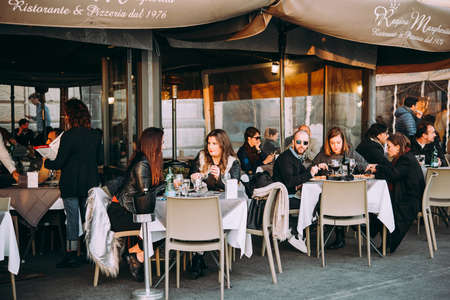 NAPLES, ITALY - 18 DECEMBER, 2017: People having dinner at the terrace of a street cafes in Naples, Campania, Italy. Editorial