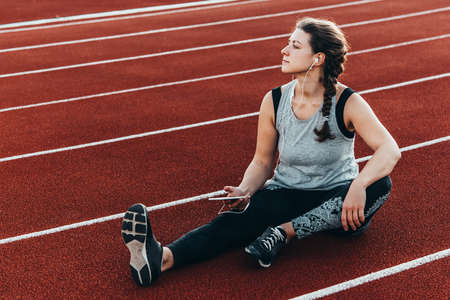 A young beautiful woman having rest with her smartphone sitting at a stadium running track.