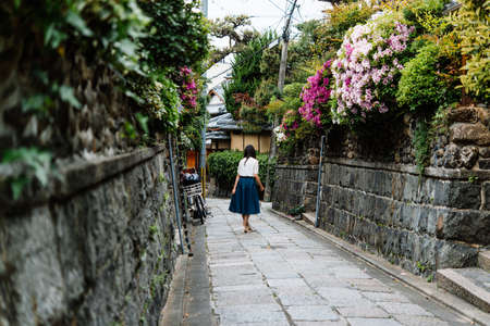 Tourists walk along one of the old streets in Kyoto, Japan. Фото со стока