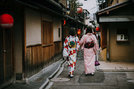 Women wearing traditional japanese kimonos walk along one of the streets in Kyoto, Japan. 新聞圖片