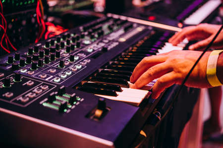 Playing music using an analog synthesizer connected to a modular synthesizer. Electronic music and professional music equipment concept. Stock Photo
