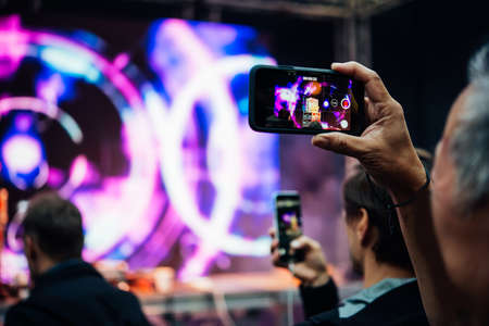 A person taking photo or video with his smartphone during a concert or a performance.