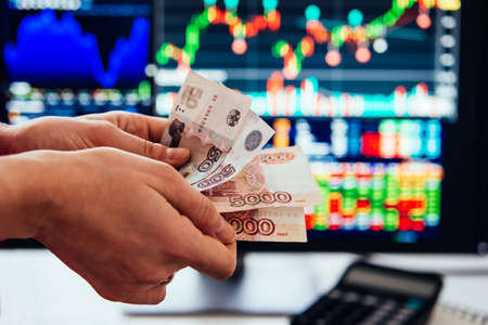 Hands holding russian currency roubles in front of the stock exchange screen showing trading graphics. Stock fotó