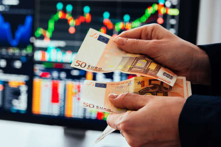 Hands holding european currency Euro in front of the stock exchange screen showing trading graphics.
