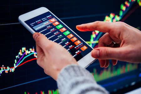 Un comerciante o un analista financiero que verifica las tendencias recientes de la bolsa de valores utilizando el teléfono inteligente.