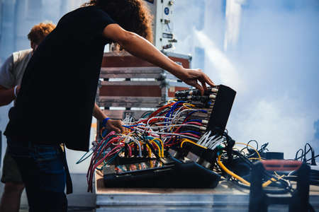 Musician performs on stage using modular synthesizers. Electronic music and professional music equipment concept.